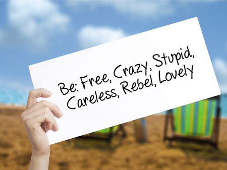 careless: Be: Free, Crazy, Stupid, Careless, Rebel, Lovely Sign on white paper. Man Hand Holding Paper with text. Isolated on holiday background.  Business concept. Stock Photo