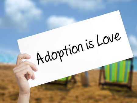 foster parenting: Adoption is Love Sign on white paper. Man Hand Holding Paper with text. Isolated on holiday background. Adoption,  Business concept. Stock Photo Stock Photo