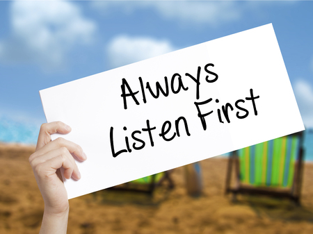 Always Listen First Sign on white paper. Man Hand Holding Paper with text. Isolated on holiday background.   Business concept. Stock Photo