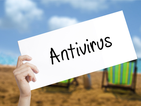 adware: Antivirus   Sign on white paper. Man Hand Holding Paper with text. Isolated on holiday background.   Business concept. Stock Photo