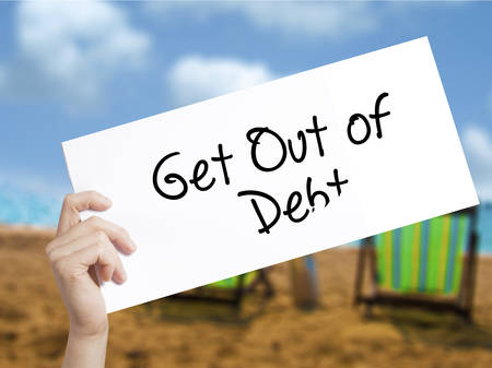 rating: Get Out of Debt Sign on white paper. Man Hand Holding Paper with text. Isolated on holiday background.  Business concept. Stock Photo
