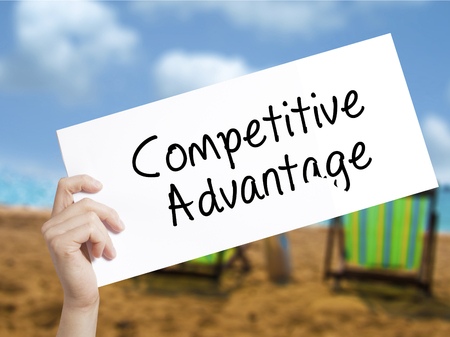 correlate: Competitive Advantage Sign on white paper. Man Hand Holding Paper with text. Isolated on holiday background.  Business concept. Stock Photo Stock Photo
