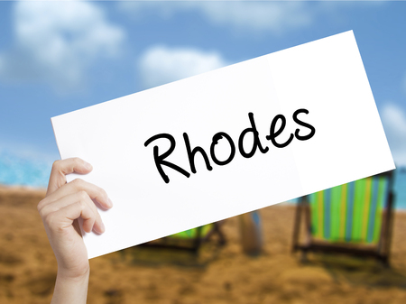 tsambika: Rhodes Sign on white paper. Man Hand Holding Paper with text. Isolated on holiday background.   Business concept. Stock Photo