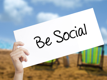 recruit help: Be Social Sign on white paper. Man Hand Holding Paper with text. Isolated on holiday background. Isolated on background. Business, technology, internet concept. Stock  Photo