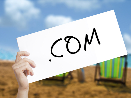 domains: .COM Sign on white paper. Man Hand Holding Paper with text. Isolated on holiday background.  Business concept. Stock Photo