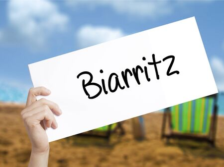 Biarritz  Sign on white paper. Man Hand Holding Paper with text. Isolated on holiday background.   Business concept. Stock Photo Banco de Imagens