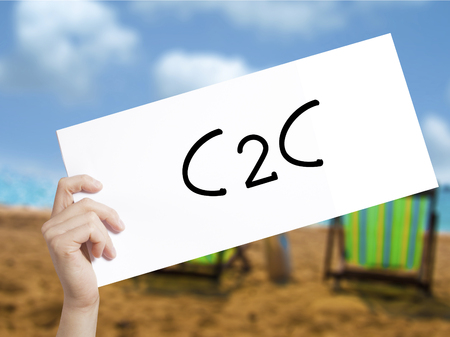 C2C Sign on white paper. Man Hand Holding Paper with text. Isolated on holiday background.  Business concept. Stock Photo