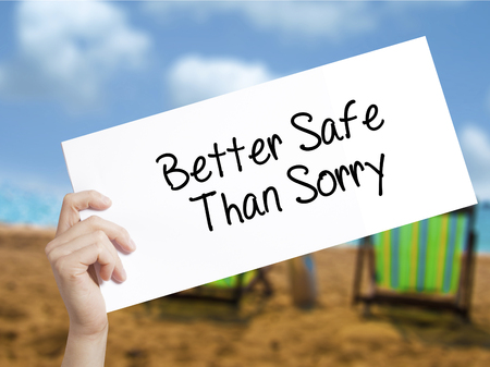 better safe than sorry: Better Safe Than Sorry Sign on white paper. Man Hand Holding Paper with text. Isolated on holiday background.  Business concept. Stock Photo