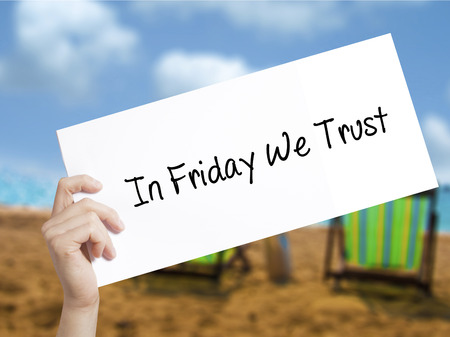 In Friday We Trust  Sign on white paper. Man Hand Holding Paper with text. Isolated on holiday background.   Business concept. Stock Photo Фото со стока