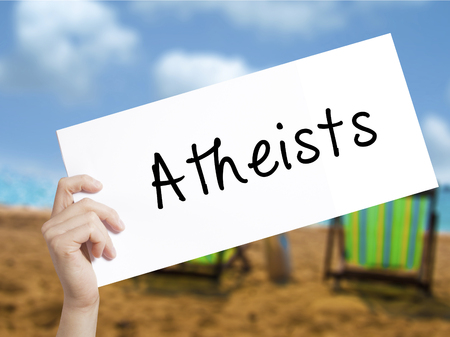 atheism: Atheists Sign on white paper. Man Hand Holding Paper with text. Isolated on holiday background.  Business concept. Stock Photo Stock Photo