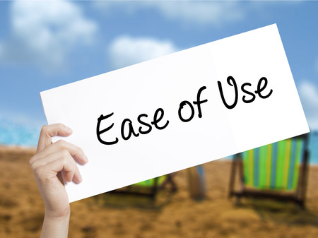 user friendly: Ease of Use Sign on white paper. Man Hand Holding Paper with text. Isolated on holiday background.  technology, internet concept.
