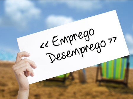 need direction: Emprego Desemprego (Employment - Unemployment in Portuguese)  Sign on white paper. Man Hand Holding Paper with text. Isolated on holiday background.  Business concept. Stock Photo