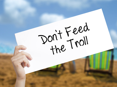 instigator: Dont Feed the Troll Sign on white paper. Man Hand Holding Paper with text. Isolated on holiday background.  Business concept. Stock Photo