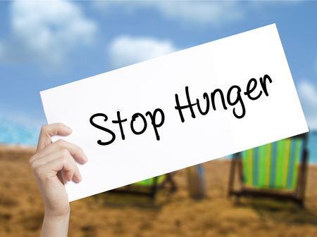 dearth: Stop Hunger Sign on white paper. Man Hand Holding Paper with text. Isolated on holiday background.  Business concept. Stock Photo