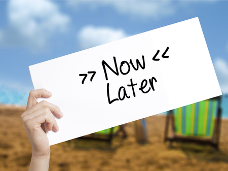 immediate: NowLater Sign on white paper. Man Hand Holding Paper with text. Isolated on holiday background.  Business concept. Stock Photo Stock Photo