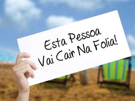 Esta Pessoa Vai Cair Na Folia! (This Person Will be at Carnaval in Portuguese) Sign on white paper. Man Hand Holding Paper with text. Isolated on holiday background.  Business concept. Stock Photo