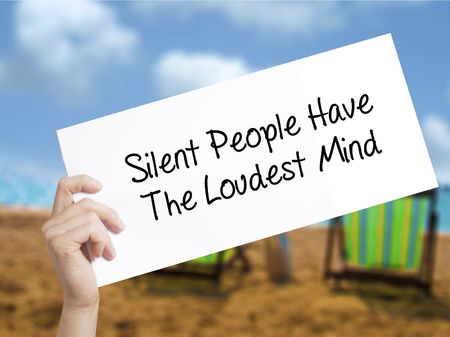 Silent People Have The Loudest Mind Sign on white paper. Man Hand Holding Paper with text. Isolated on holiday background.  Business concept. Stock Photo Stock Photo