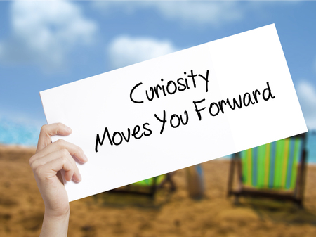 faq's: Curiosity Moves You Forward Sign on white paper. Man Hand Holding Paper with text. Isolated on holiday background.  Business concept. Stock Photo