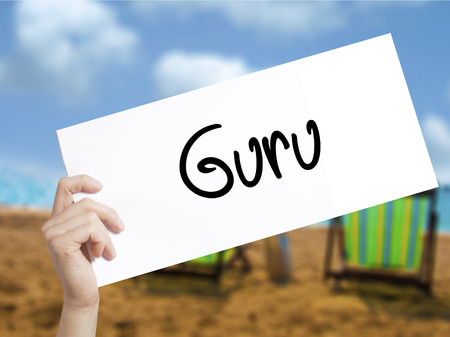 Guru Sign on white paper. Man Hand Holding Paper with text. Isolated on holiday background.  Business concept. Stock Photo
