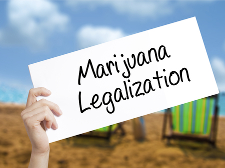 legislators: Marijuana Legalization Sign on white paper. Man Hand Holding Paper with text. Isolated on holiday background. Live,  Business concept. Stock Photo