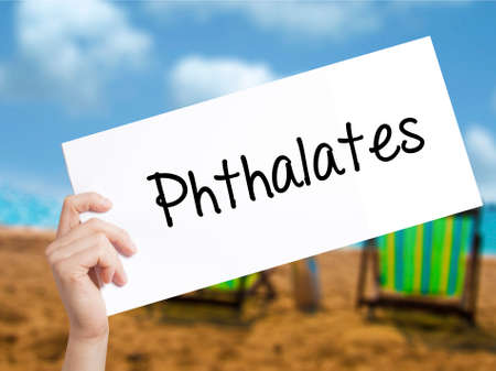 phthalates: Phthalates  Sign on white paper. Man Hand Holding Paper with text. Isolated on holiday background.  Business concept. Stock Photo