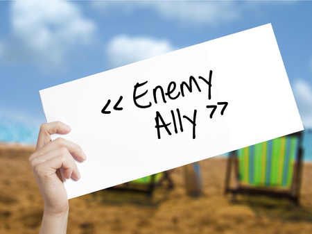Enemy - Ally Sign on white paper. Man Hand Holding Paper with text. Isolated on holiday background.  Business concept. Stock Photo Stock Photo