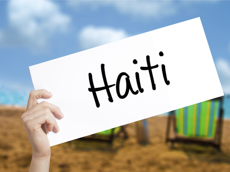 haitian: Haiti Sign on white paper. Man Hand Holding Paper with text. Isolated on holiday background.   Business concept. Stock Photo