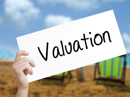 multiplying: Valuation Sign on white paper. Man Hand Holding Paper with text. Isolated on holiday background.  Business concept. Stock Photo