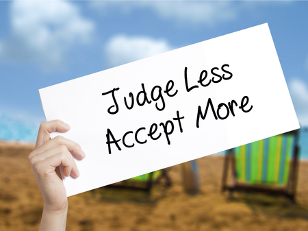 acceptable: Judge Less Accept More Sign on white paper. Man Hand Holding Paper with text. Isolated on holiday background.  Business concept. Stock Photo