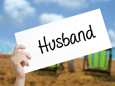 ex wife: Husband Sign on white paper. Man Hand Holding Paper with text. Isolated on holiday background.  Business concept. Stock Photo