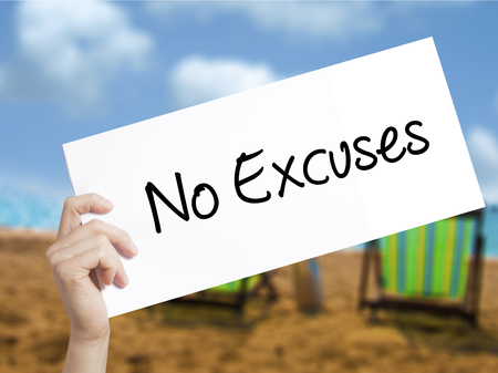 No Excuses Sign on white paper. Man Hand Holding Paper with text. Isolated on holiday background. Business concept. Stock Photo