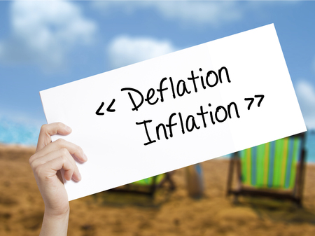Deflation - Inflation Sign on white paper. Man Hand Holding Paper with text. Isolated on holiday background.  Business concept. Stock Photo