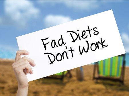 Fad Diets Dont Work Sign on white paper. Man Hand Holding Paper with text. Isolated on holiday background.   Business concept. Stock Photo