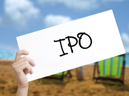 public offering: IPO (Initial Public Offering)   Sign on white paper. Man Hand Holding Paper with text. Isolated on holiday background.  Business concept. Stock Photo Stock Photo