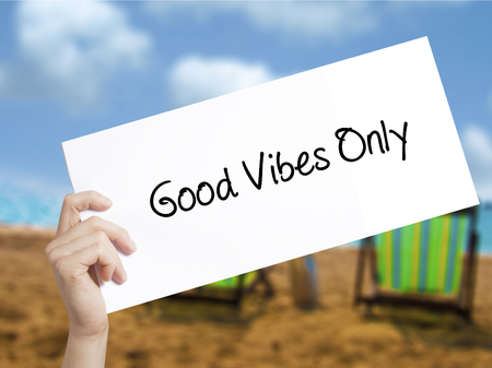 vibe: Good Vibes Only  Sign on white paper. Man Hand Holding Paper with text. Isolated on holiday background.   Business concept. Stock Photo