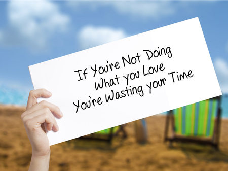 what if: If Youre Not Doing What you Love Youre Wasting your Time Sign on white paper. Man Hand Holding Paper with text. Isolated on holiday background.  technology, internet concept.