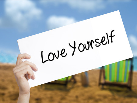 selfish: Love Yourself Sign on white paper. Man Hand Holding Paper with text. Isolated on holiday background.   Business concept. Stock Photo