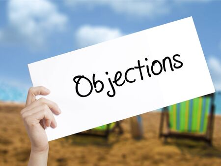 objections: Objections  Sign on white paper. Man Hand Holding Paper with text. Isolated on holiday background.   Business concept. Stock Photo