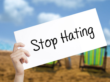 bigotry: Stop Hating  Sign on white paper. Man Hand Holding Paper with text. Isolated on holiday background.  Business concept. Stock Photo Stock Photo