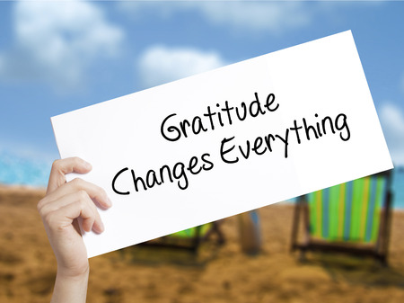 humility: Gratitude Changes Everything Sign on white paper. Man Hand Holding Paper with text. Isolated on holiday background.   Business concept. Stock Photo