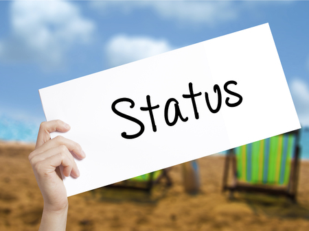 Status Sign on white paper. Man Hand Holding Paper with text. Isolated on holiday background.  Business concept. Stock Photo Stock Photo