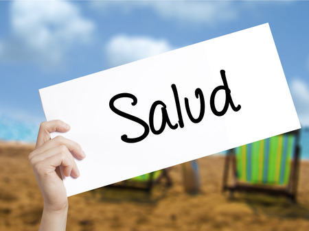 Salud (Health in Spanish) Sign on white paper. Man Hand Holding Paper with text. Isolated on holiday background.  Business concept. Stock Photo Stock Photo