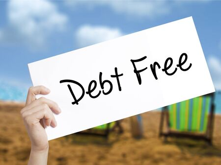 rating: Debt Free Sign on white paper. Man Hand Holding Paper with text. Isolated on holiday background.   Business concept. Stock Photo