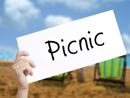 Picnic Sign on white paper. Man Hand Holding Paper with text. Isolated on holiday background.   Business concept. Stock Photo