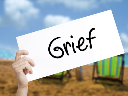 Grief Sign on white paper. Man Hand Holding Paper with text. Isolated on holiday background.  Business concept. Stock Photo