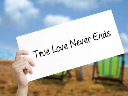 waits: True Love Never Ends Sign on white paper. Man Hand Holding Paper with text. Isolated on holiday background.   Business concept. Stock Photo