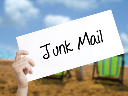 solicitors: Junk Mail Sign on white paper. Man Hand Holding Paper with text. Isolated on holiday background.   Business concept. Stock Photo Stock Photo