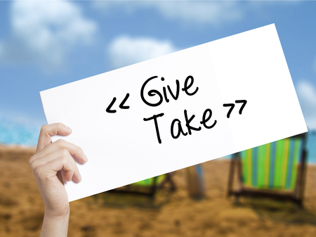 Give - Take Sign on white paper. Man Hand Holding Paper with text. Isolated on holiday background.  Business concept. Stock Photo