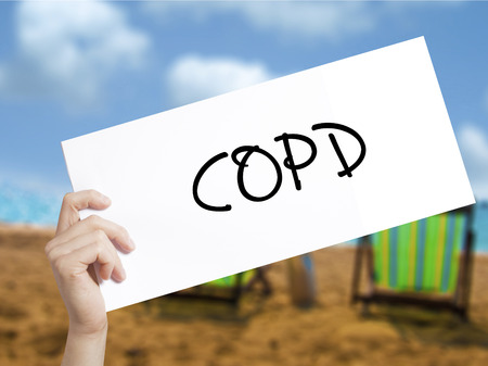 COPD Sign on white paper. Man Hand Holding Paper with text. Isolated on holiday background.   Business concept. Stock Photo