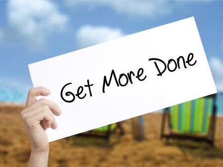 Get More Done Sign on white paper. Man Hand Holding Paper with text. Isolated on holiday background.  technology, internet concept.
